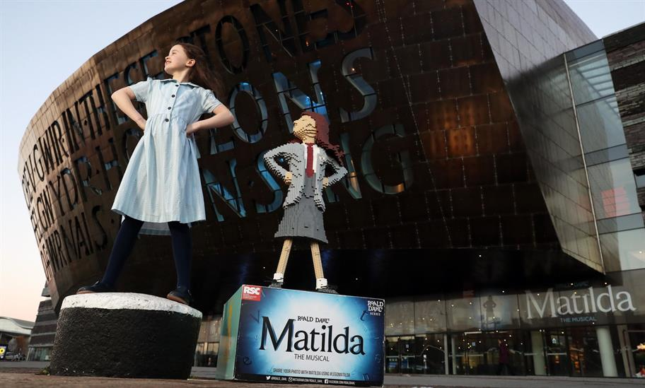 Girl playing Matilda standing on a bollard next to a Lego Matilda outside the Millennium Centre