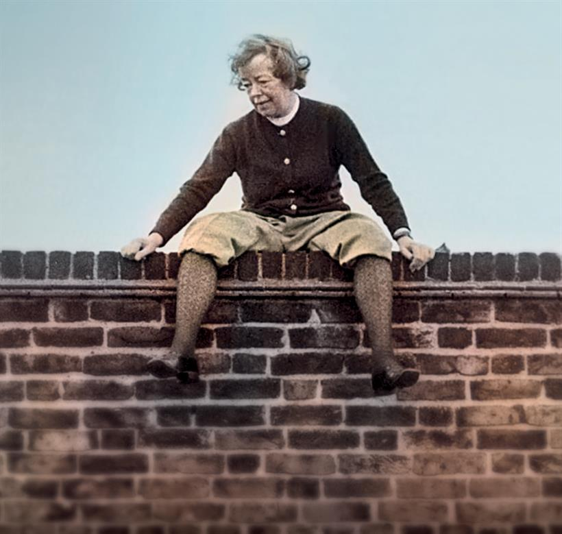 Joan Littlewood sitting on a brick wall