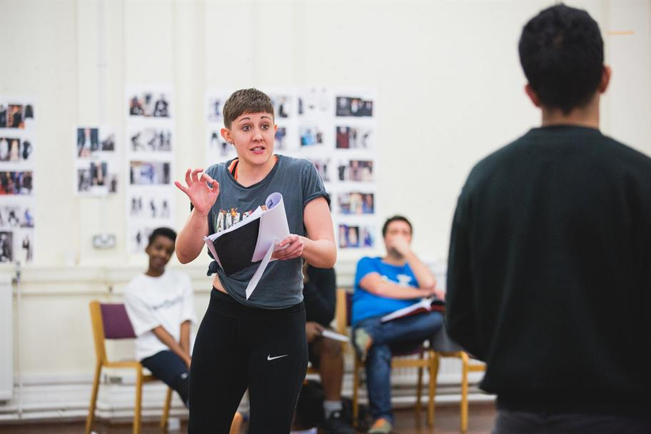 Charlotte holding a script and gesticulating in a rehearsal room
