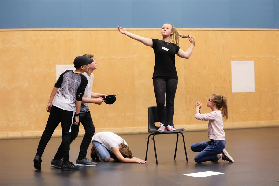 A girl stands on a chair during rehearsals as others kneel beneath her.
