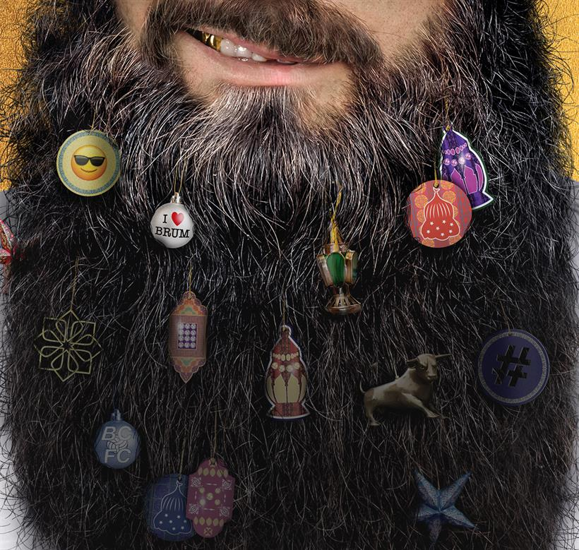 Man from mouth down to the bottom of a long dark-haired beard, studded with decorations