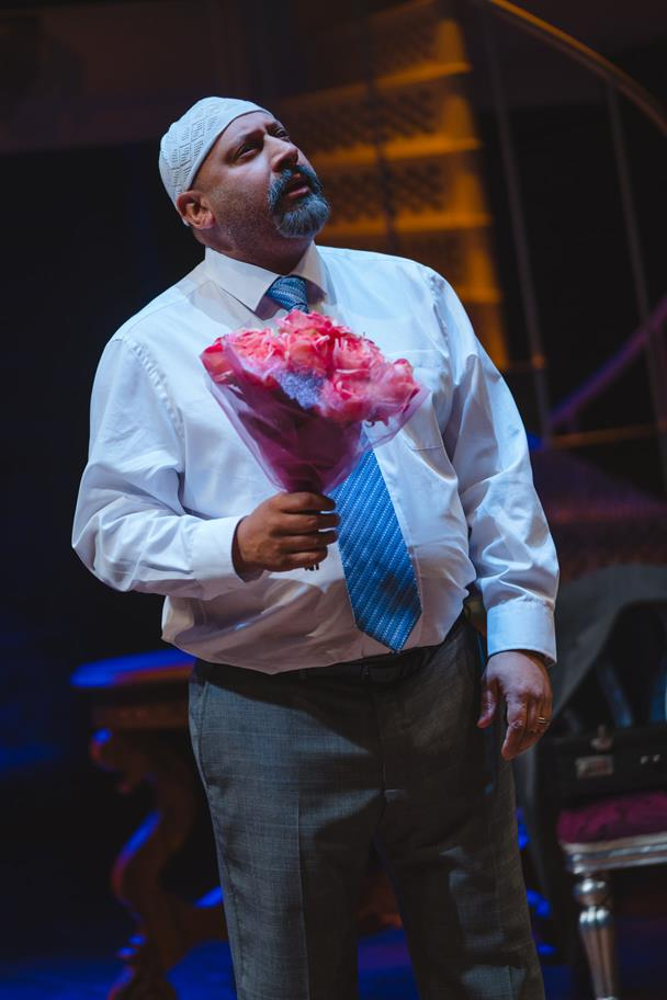 Man in smart clothing holding bouquet of roses.