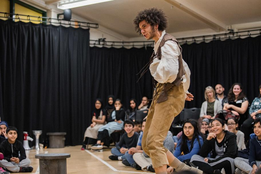 audience of school children in a school hall watching  a man in sandy cropped trousers and a waistcoat perform