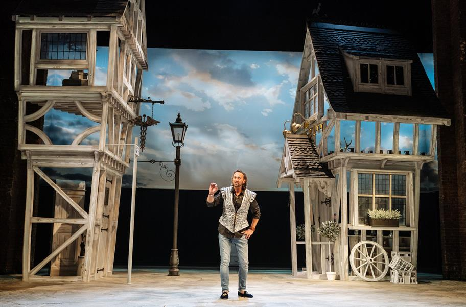 Man standing on a stage gesticulating between two frames of wooden houses