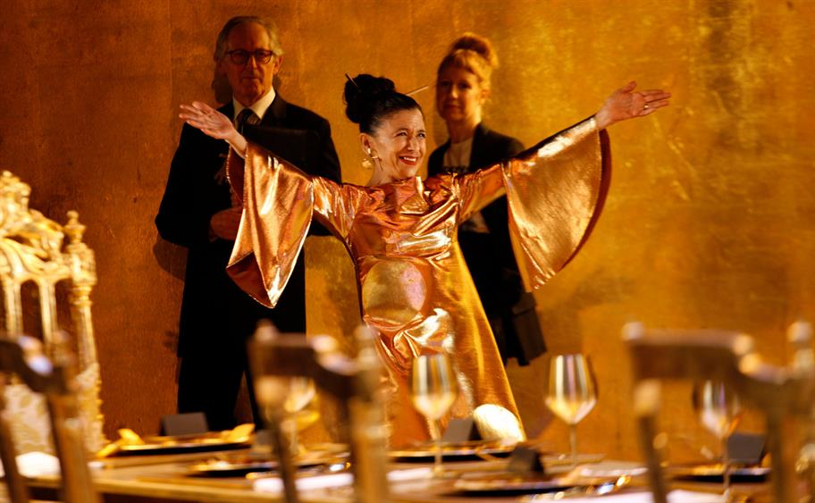 A woman in a bright gold dress raises her arms in greeting.