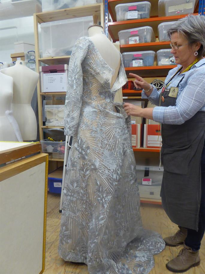 A Costumier adjusting a silver dress on a tailor's dummy