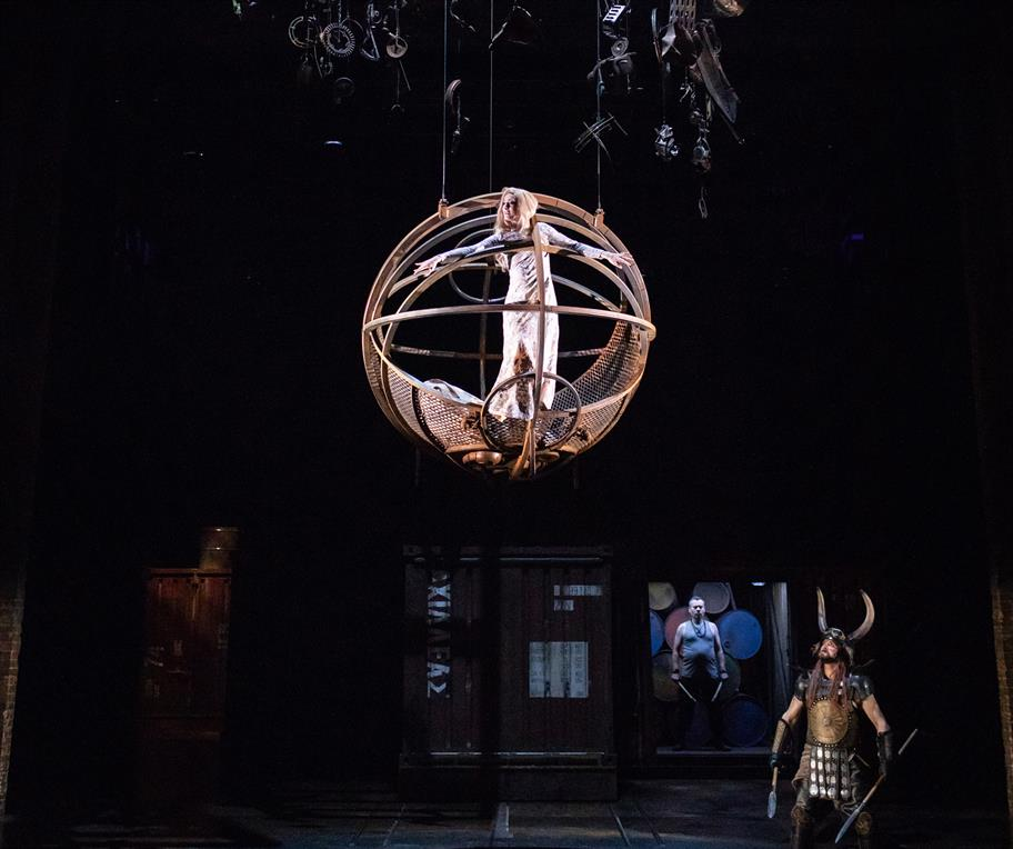 Daisy as Helen being lowered down to the stage in a metal sphere dressed in a silver dress