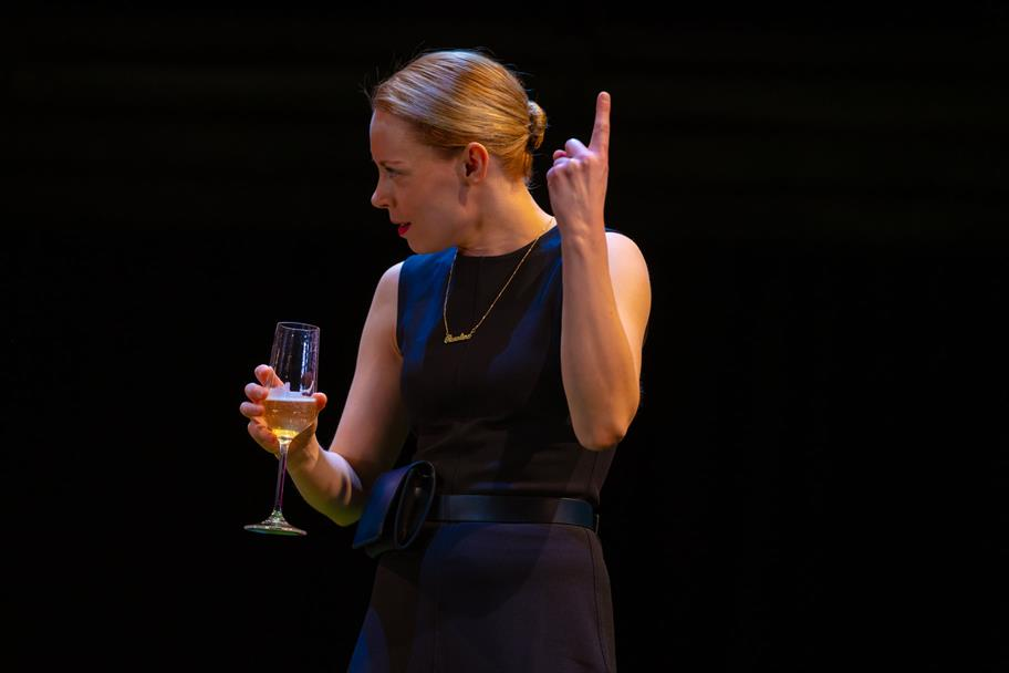 A woman in a black dress holding a glass of champagne.