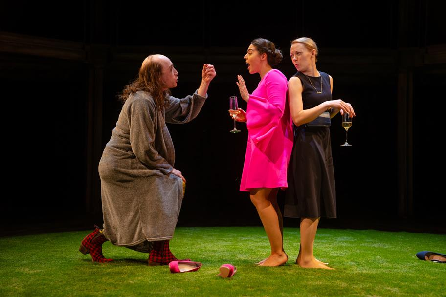 A man in a dressing gown bends before two women in elegant dresses.