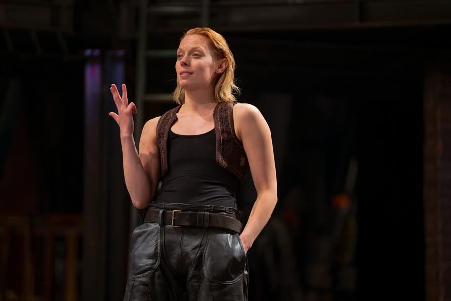 A woman in a black vest and leather trousers.