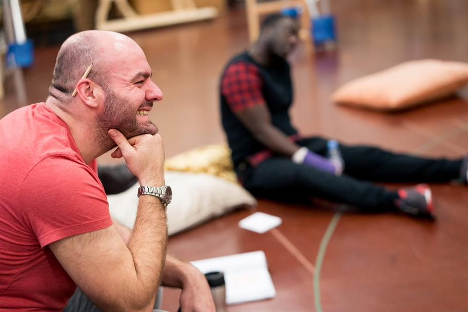 Two men sit on the floor in rehearsal, the man in the foreground smiling as he rests his chin on his hand.