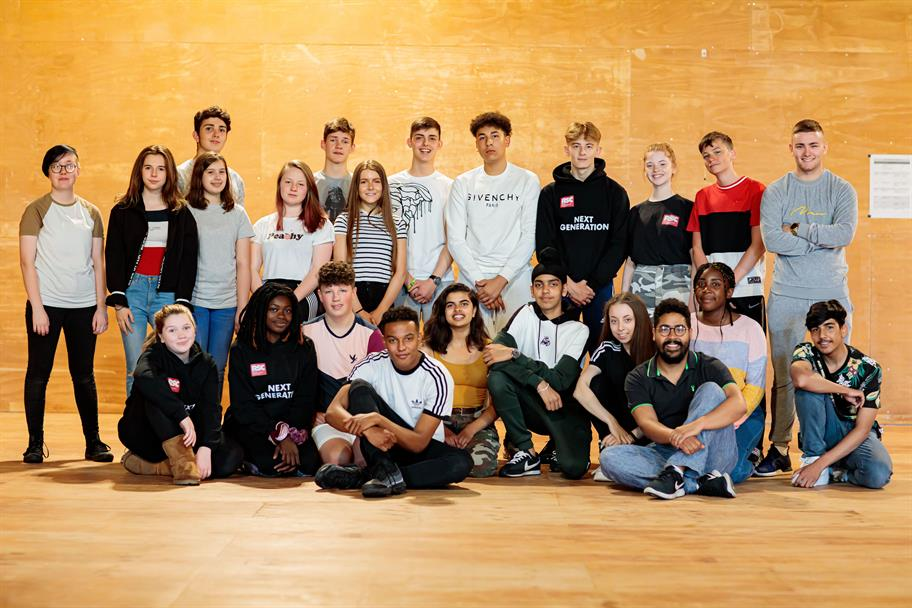 A group of young actors pose for a group shot in a rehearsal room.
