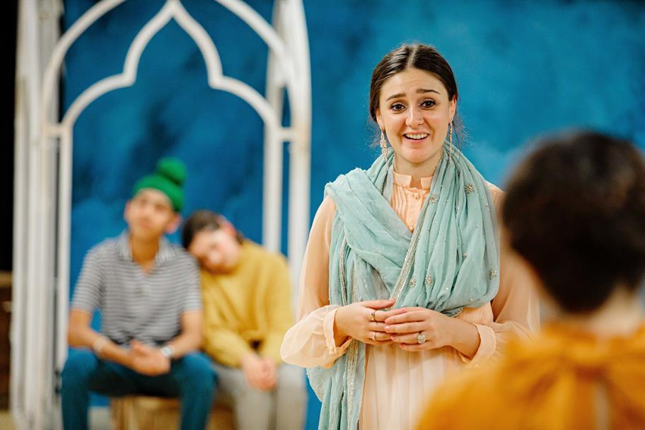 Yasmin Taheri as Portia with her hands clasped. A young couple site behind her.