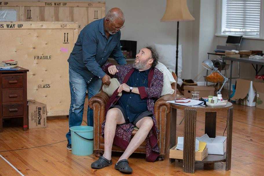 A man helps another man sat in a brown leatehr armchair.