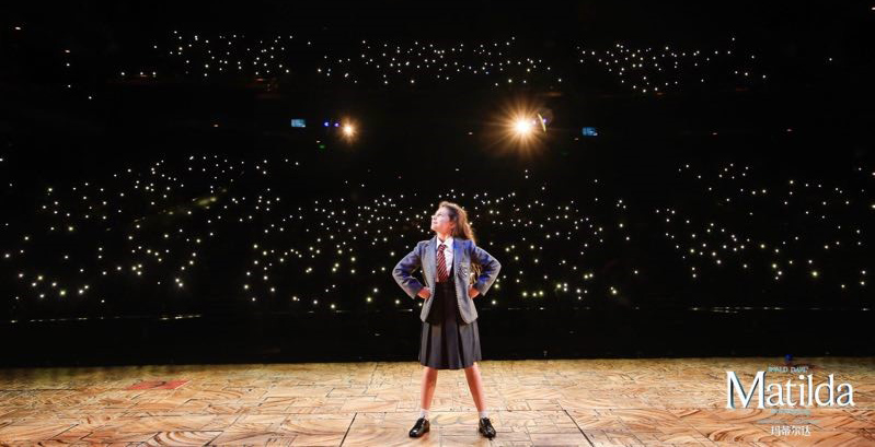 A girl in school uniform strikes a pose on stage in a dark auditorium lit up by the lights from the audience members' phones.