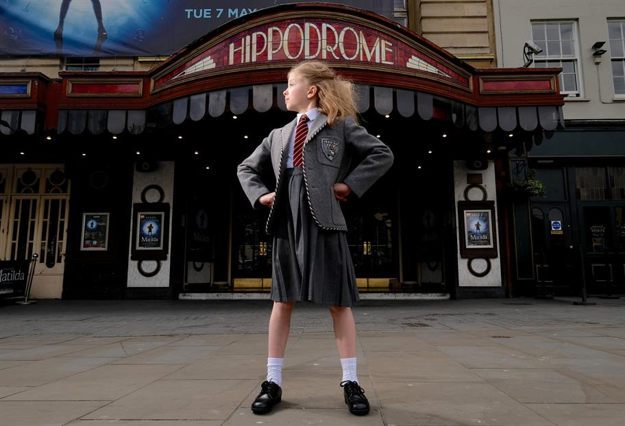 A girl in a school uniform does the Matilda pose in front of the Bristol Hippodrome.
