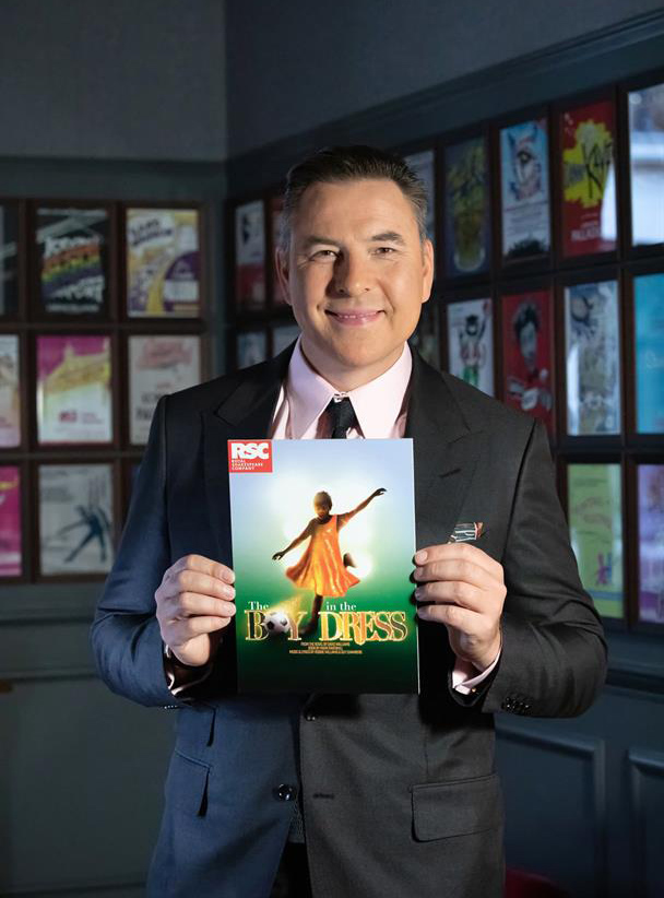 David Walliams holding up the RSC artwork for The Boy in the Dress