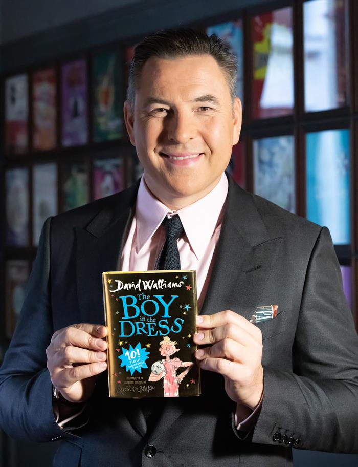 David Walliams holding a copy of The Boy in the Dress.
