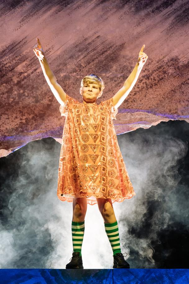 A boy in football socks and a bright orange dress stands with his fingers pointing to the sky