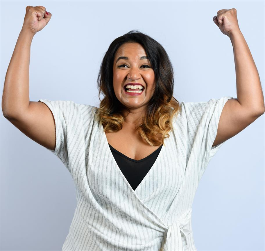 Natasha Lewis smiling with arms in the air - jubilant!