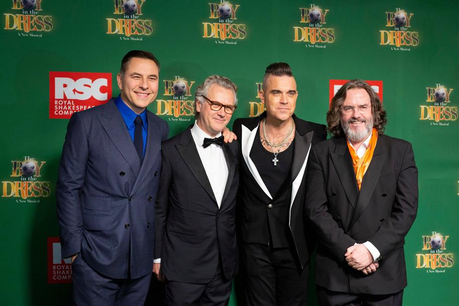 David Walliams, Guy Chambers, Robbie Williams and Gregory Doran standing dressed smartly in front of a The Boy in the dress branded green screen