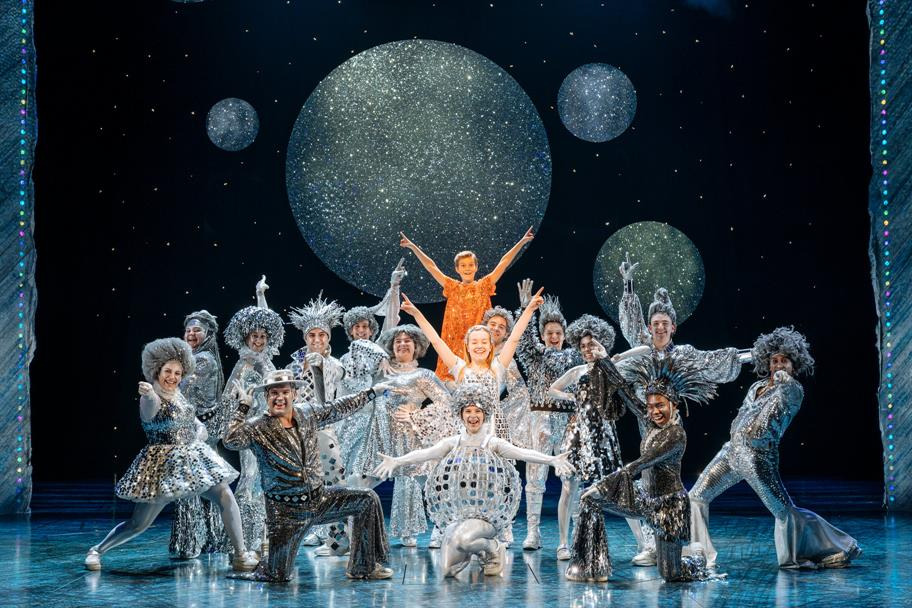 A Group of people on stage posed in sparkly costumes at the end of a dance