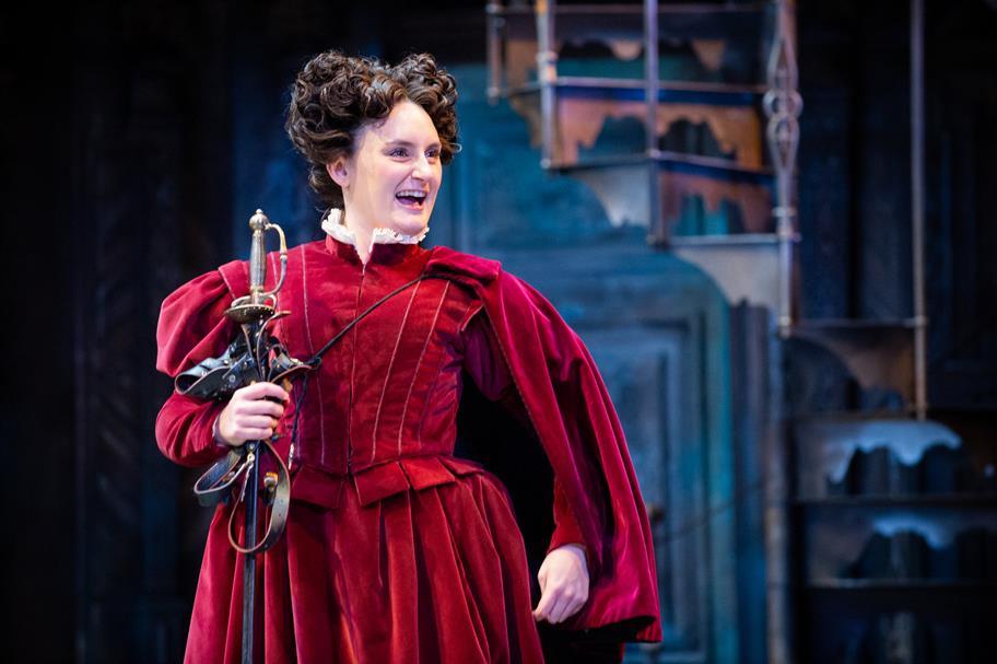 A woman in an Elizabethan dress holds a sword.