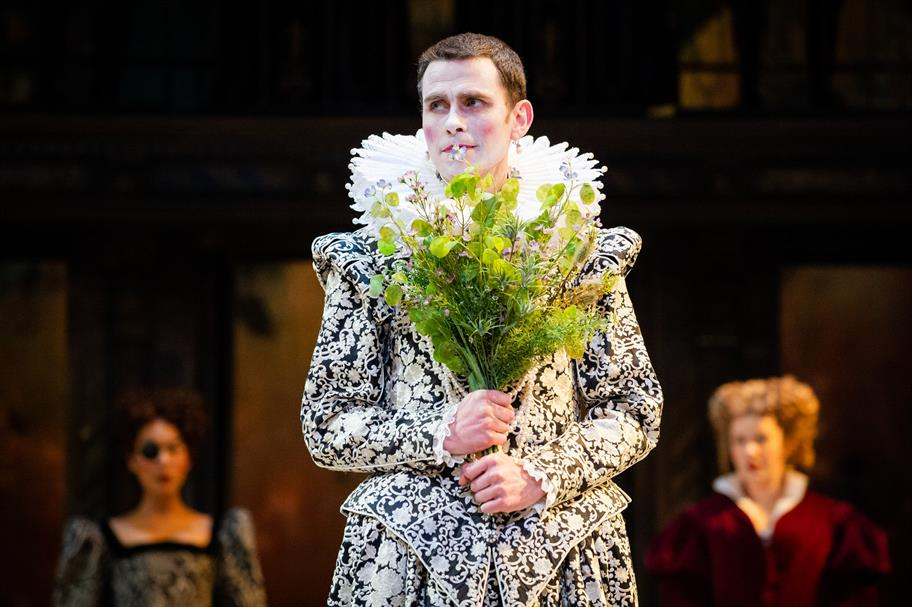 A man in white make up and a black and white fitted jacket with a ruff holds a bouquet of wild flowers.