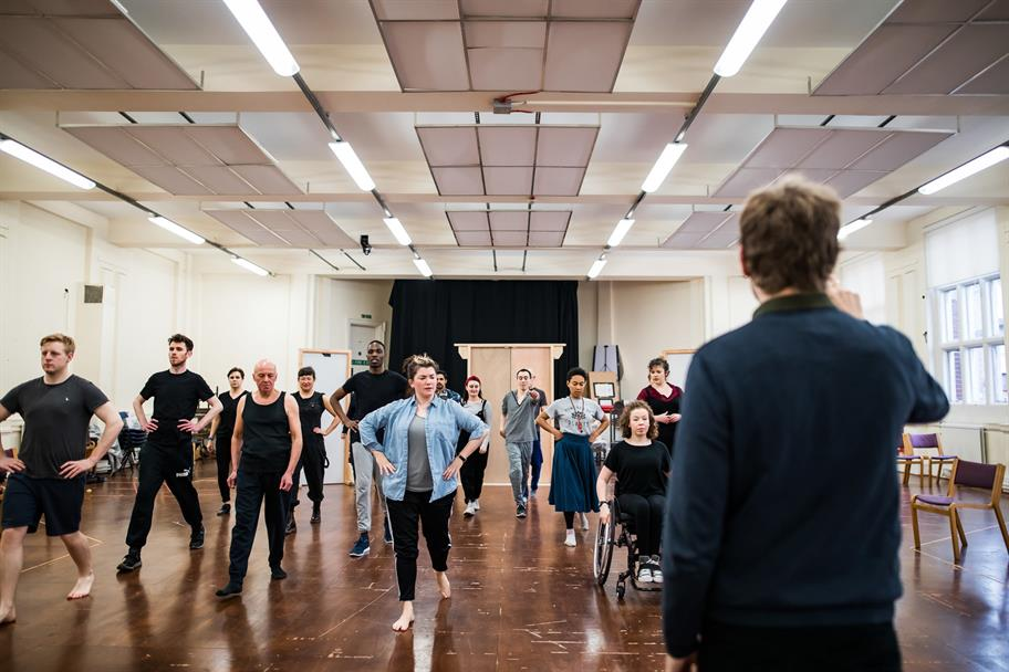 Cast in a rehearsal room dancing in formation