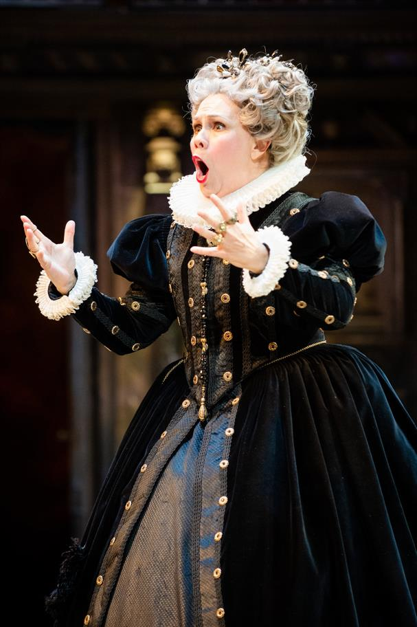 Woman dressed in black ornate Elizabethan gown with white ruff, hands extended in front of her looking shocked