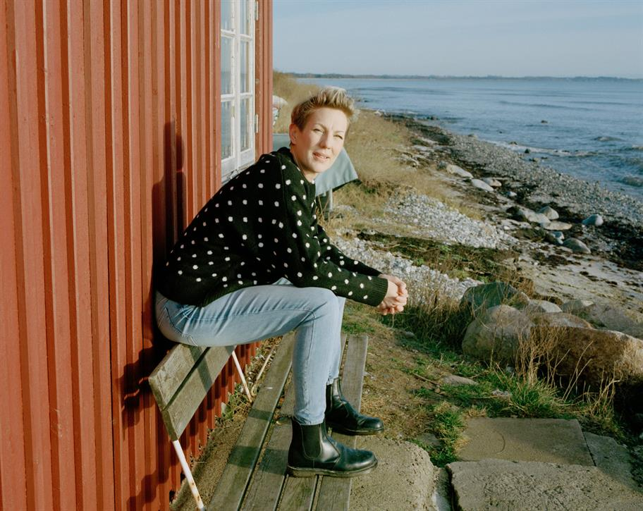 Maria Aberg seated on a piece of broken bench next to the sea, behind her is an orange corrugated building