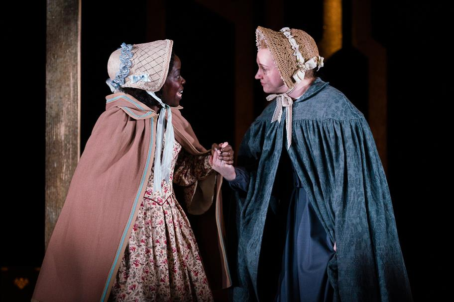 Two women in cloaks and wicker bonnets hold hands