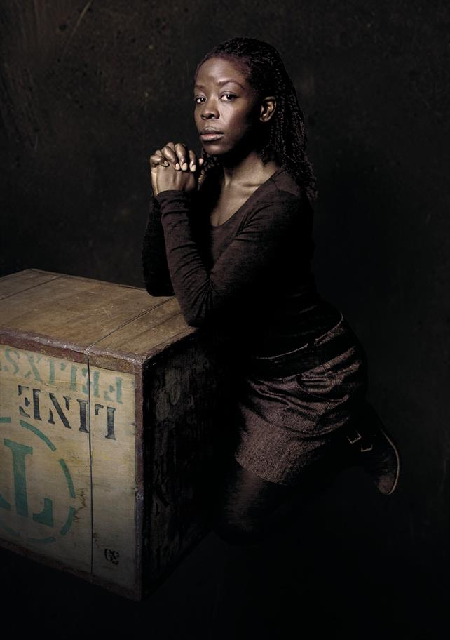 A woman clasps her hands together, leaning on a wooden crate.
