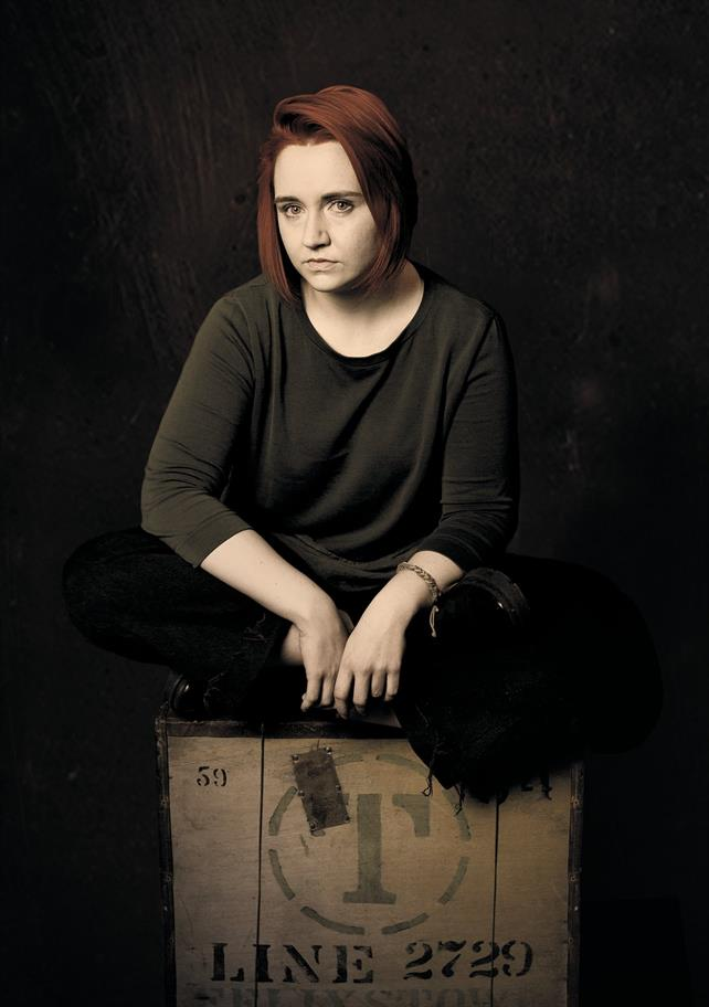 A woman sits cross-legged on a wooden crate.