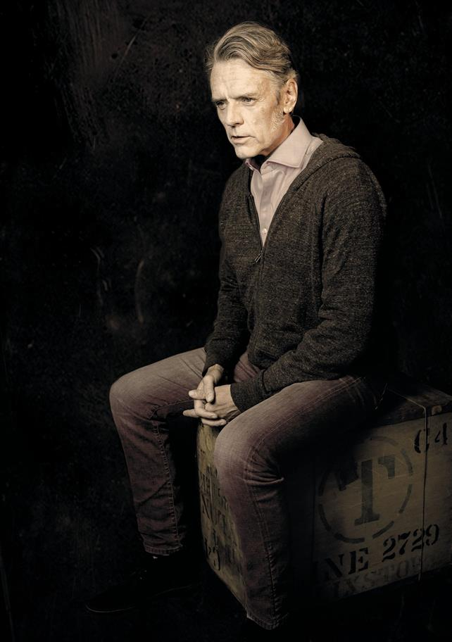 A man in a shirt and cardigan sits pensively on a wooden crate.