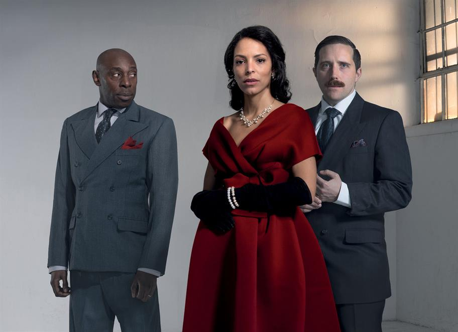 Two men in grey suits stand by a woman in a deep red gown.