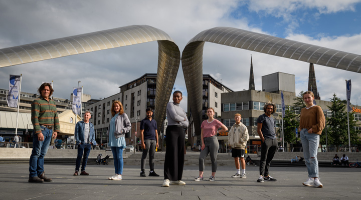 Group of people standing in front of a striking metal sculpture in Millennium Square