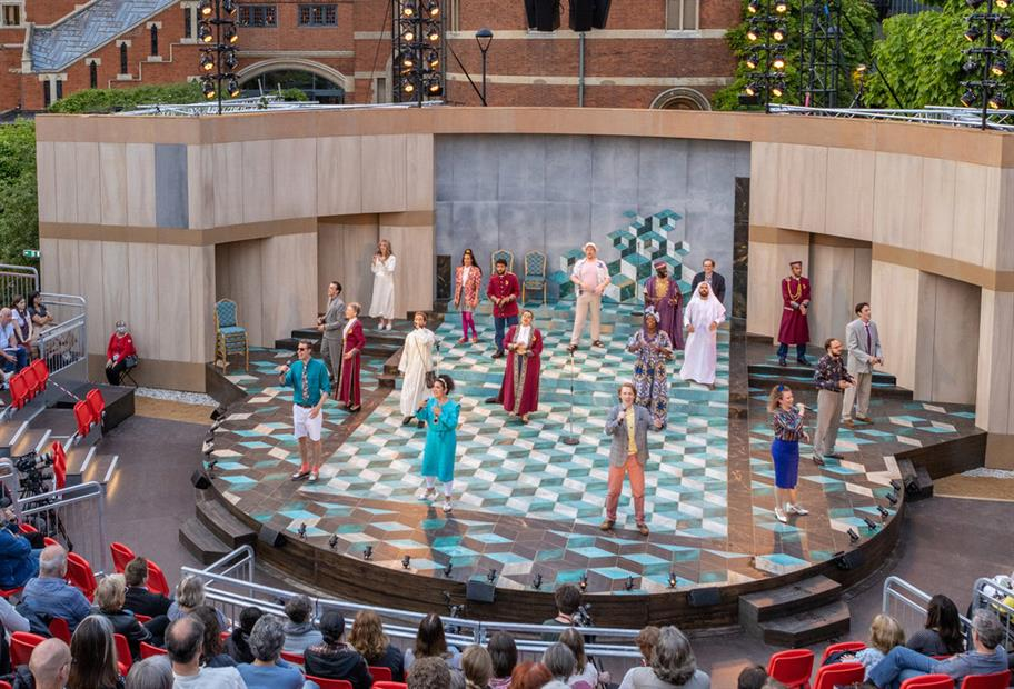 actors on the chequered stage in front of an audience in the Garden Theatre during daylight
