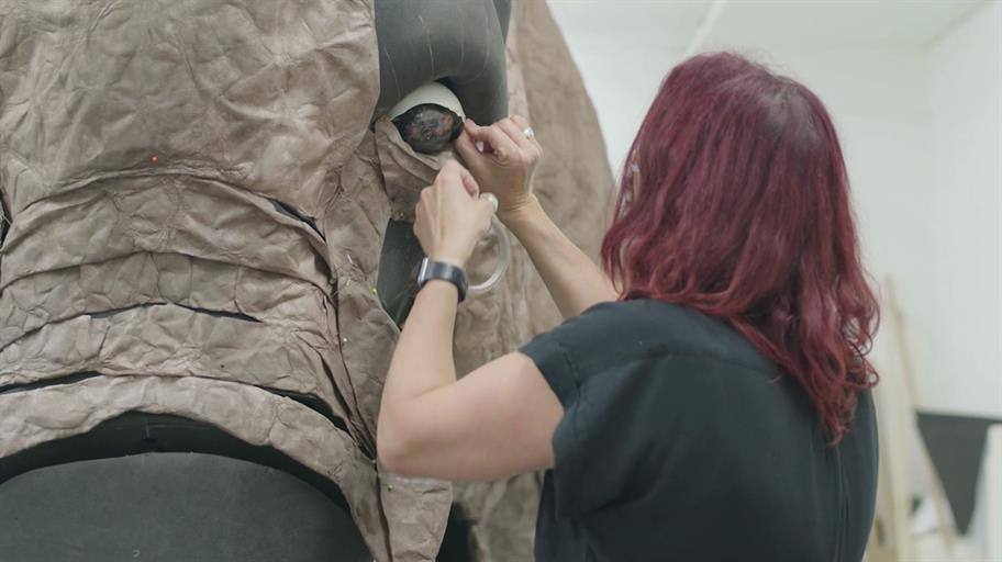 woman working on a giant elephant puppet with a detail from the elephant's face and eye