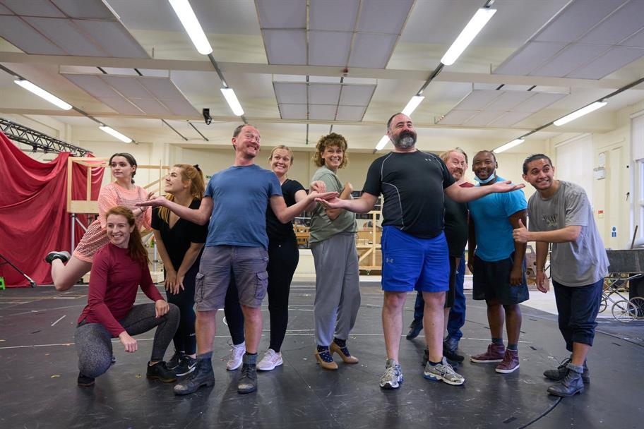 The cast in rehearsal, posing cheerily while looking to the front of the stage, with pieces of wooden scenery behind them.
