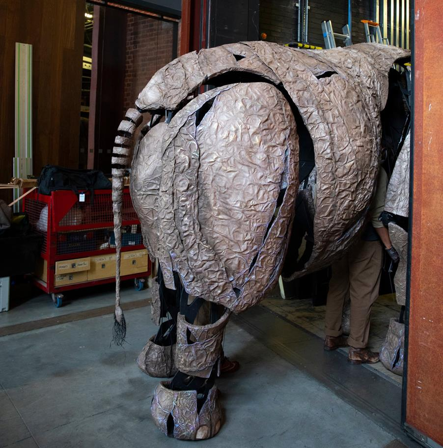 A full size grey elephant puppet pictured from behind, inside the theatre building