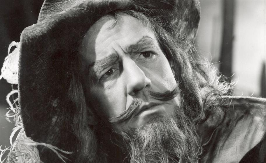 A black and white photo of Michael Hordern as Jaques, with a pointy moustache and long hair
