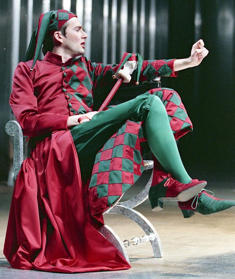 David Tennant, seated, dressed as a jester in red and green