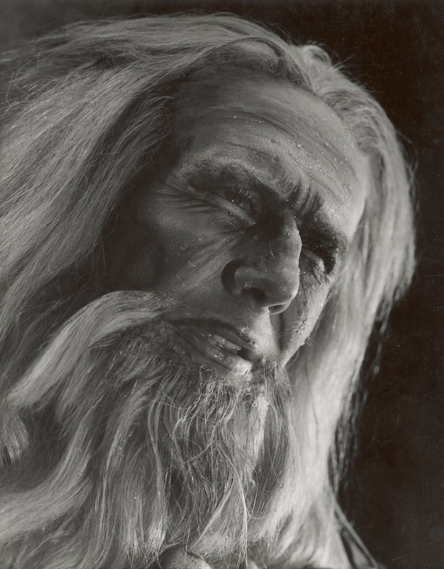 Balck and white headshot of an old man with long streaming hair and beard