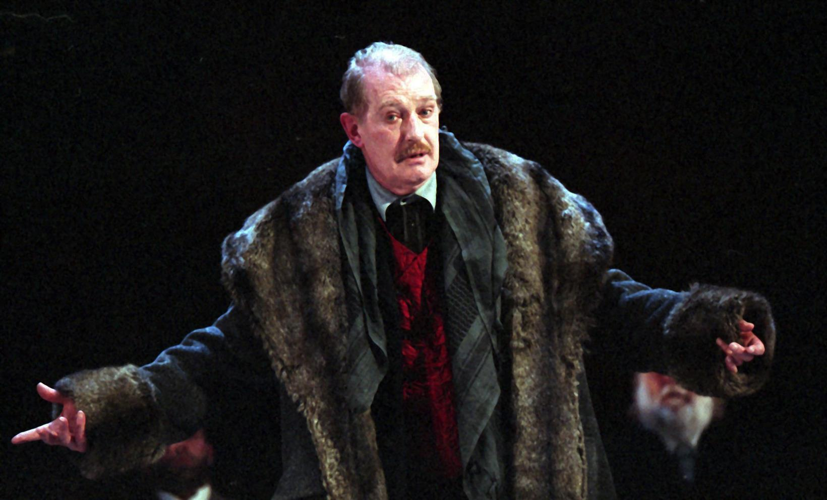 Bare-headed older man with moustache wearing a heavy fur-trimmed coat and holding out his arms