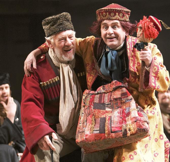 Ian McKellen as King Lear in a long red coat, with the Fool, played by Sylvester McCoy, who is wearing colourful clothes and holding a puppet