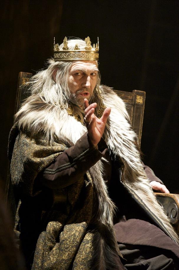 Man sitting on throne in a fur-lined coat and wearing a golden crown