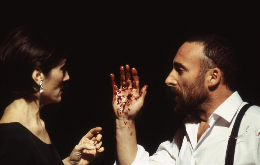 A short-haired woman looks intently at a bearded man holding up a bloody hand