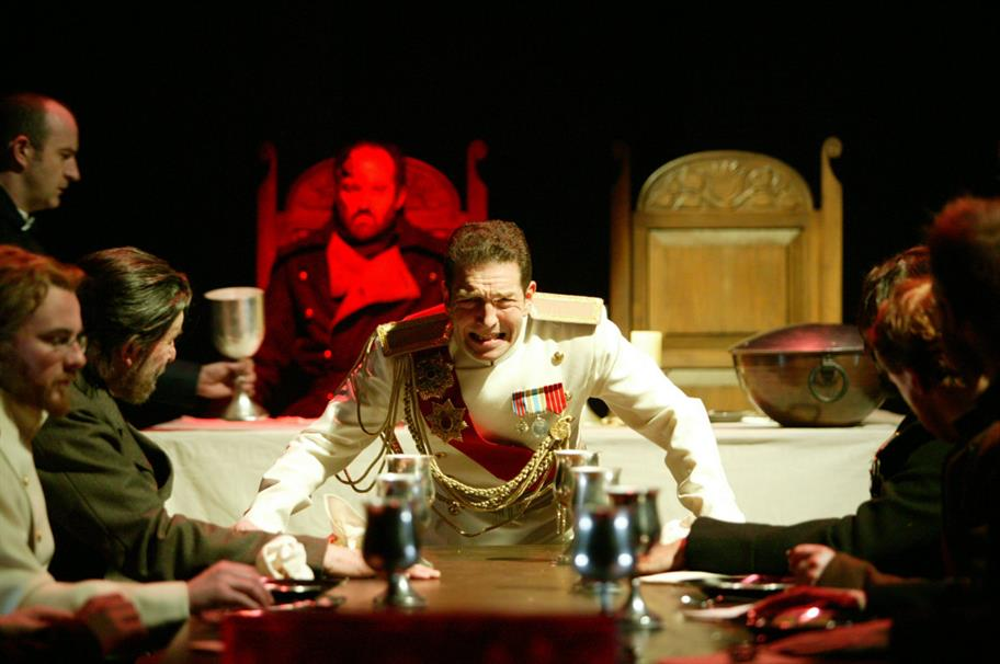 Macbeth in his white military uniform is haunted by the red-lit ghost of Banquo, sitting behind him at the banquet.