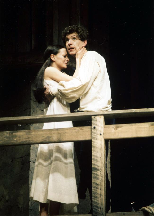 A tearful young woman in nightdress embraces a young man in light full-sleeved shirt on a wooden balcony